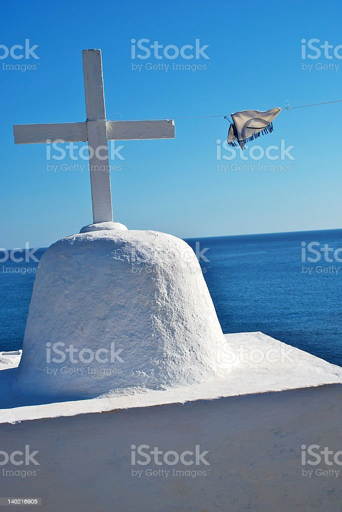 White cross of a greek chapel, blue sea on background stock photo