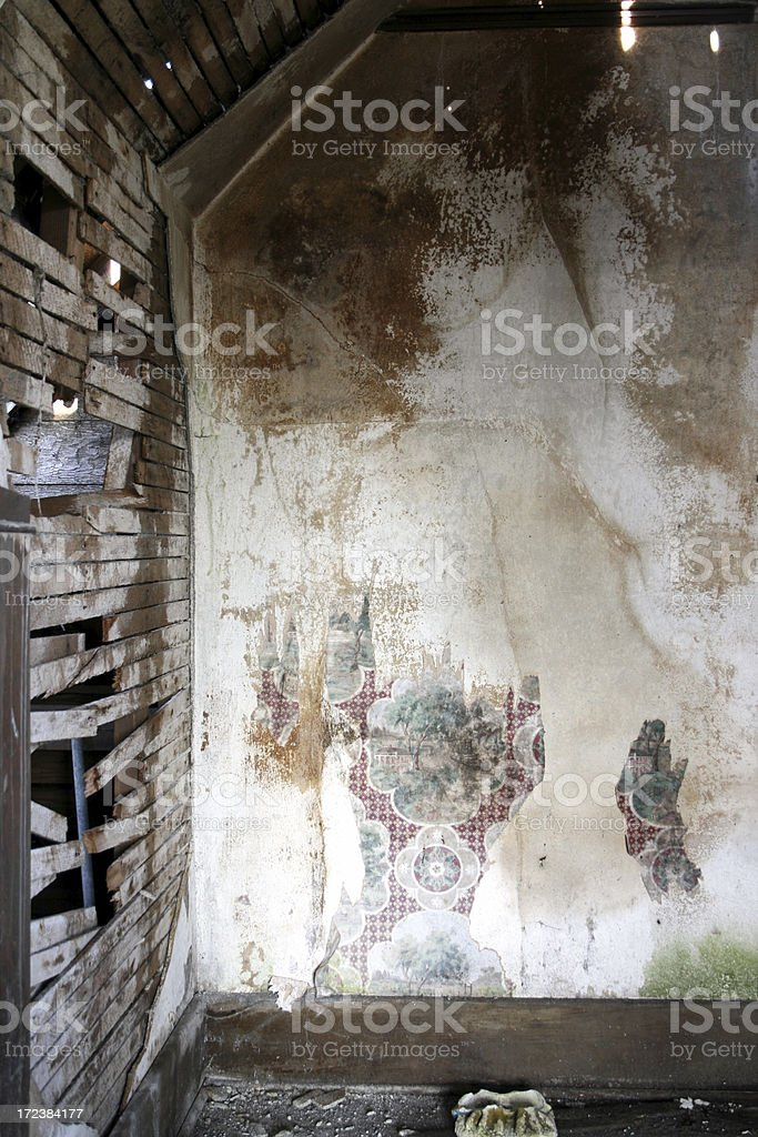 White crumbling water damaged plaster walls with wallpaper royalty-free stock photo