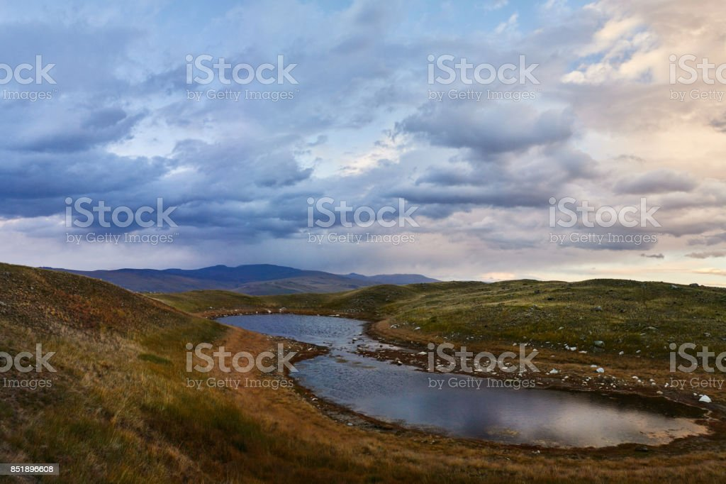 White Cumulus clouds come down from the mountains, autumn landscape in the steppe. The Ukok Plateau In The Altai. Fabulous cold landscapes. Anyone around stock photo