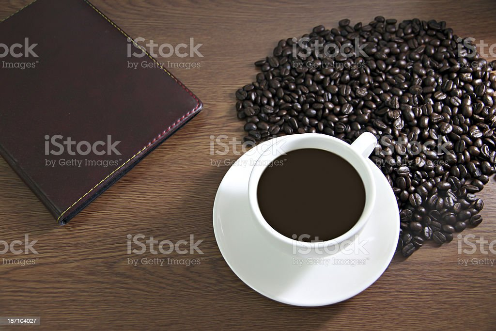 White cup and book on the table old wood. royalty-free stock photo