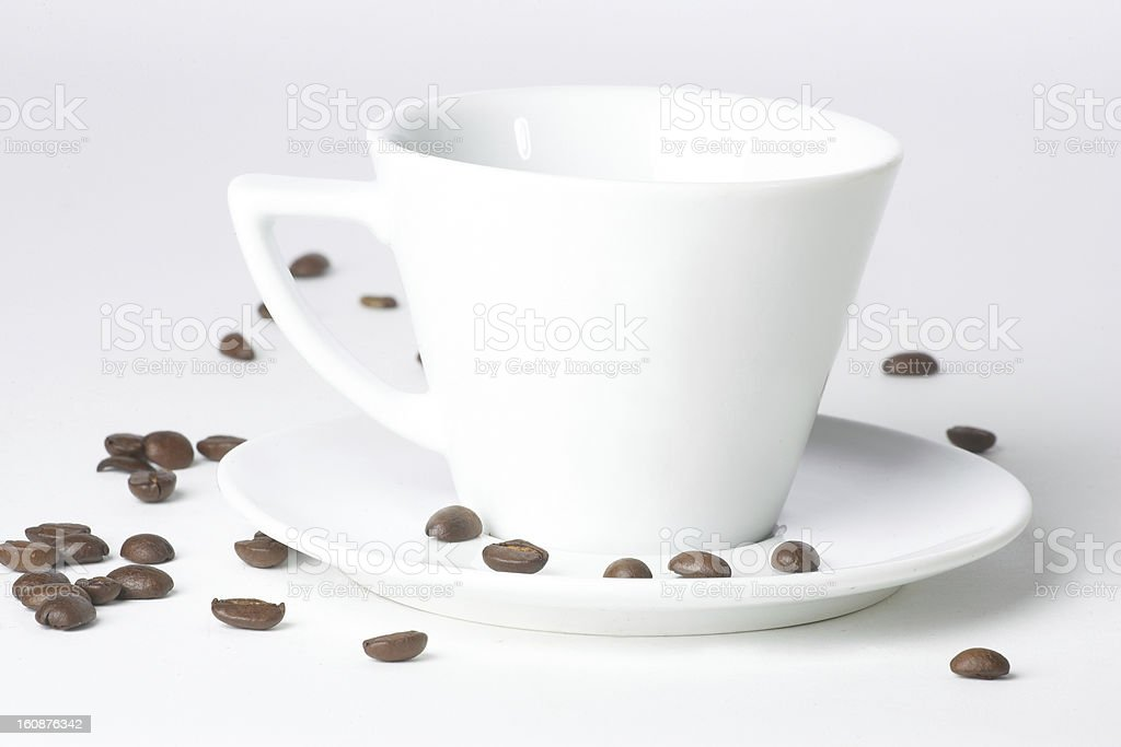 white cup and some coffee beans near it royalty-free stock photo