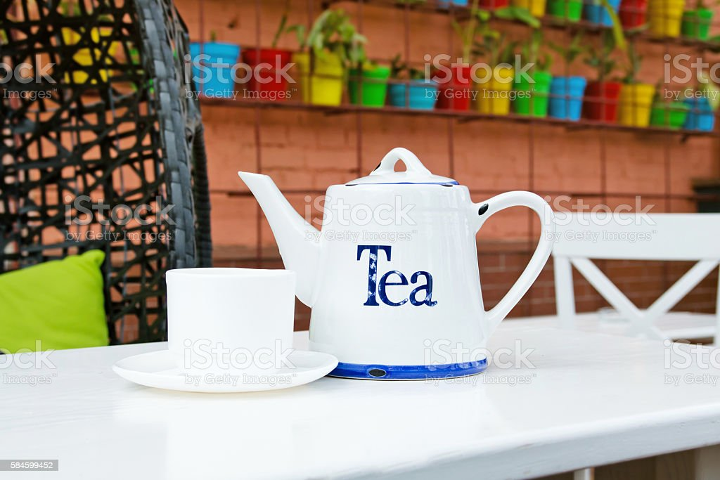 White cup and teapot tea in outdoor cafee stock photo
