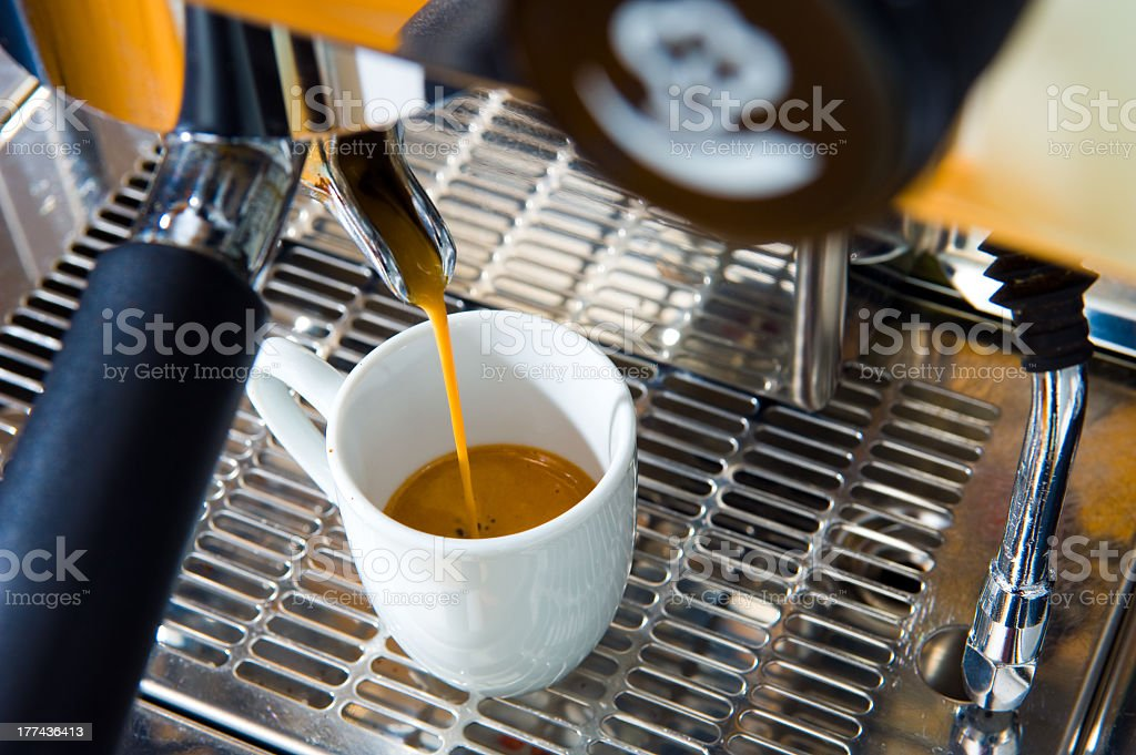 White cup being filled up in an espresso machine stock photo