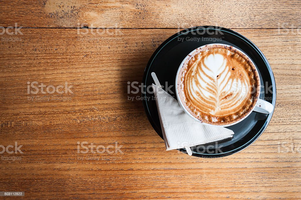 White cup of cappucino with napkin on a wood background stock photo