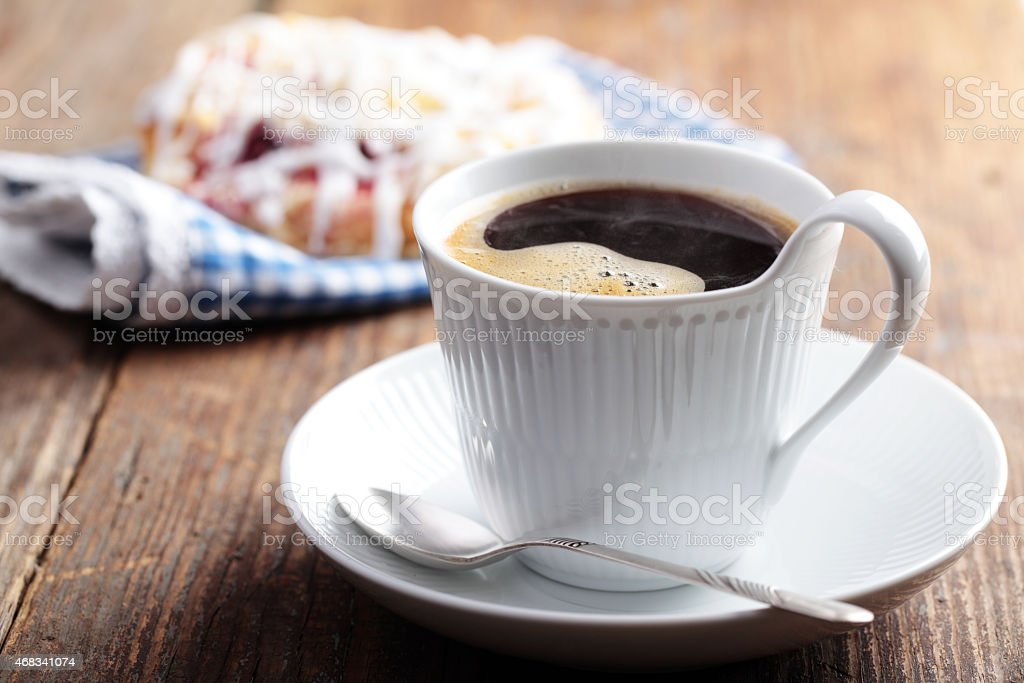White cup of coffee and cinnamon roll on wooden table  stock photo