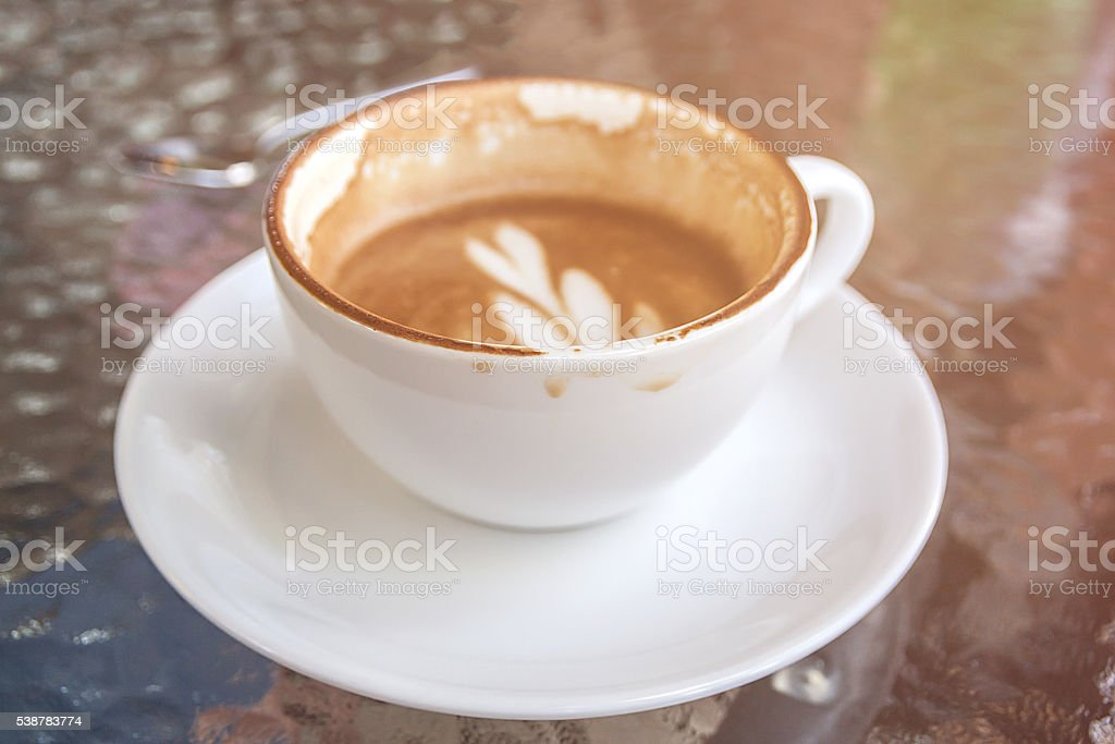 white cup of coffee latte, half drank in the cup stock photo