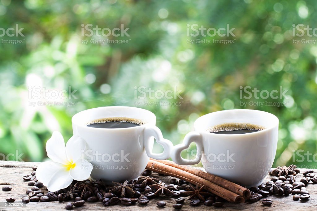 White cup of coffee on wooden, Flower, coffee beans, cinnamon stock photo