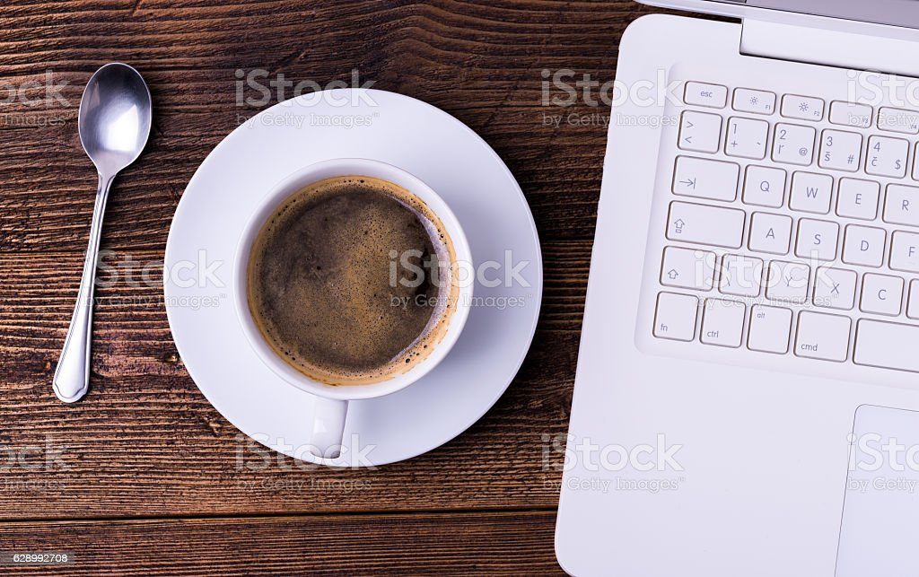 White cup of coffee with spoon and notebook on table. stock photo