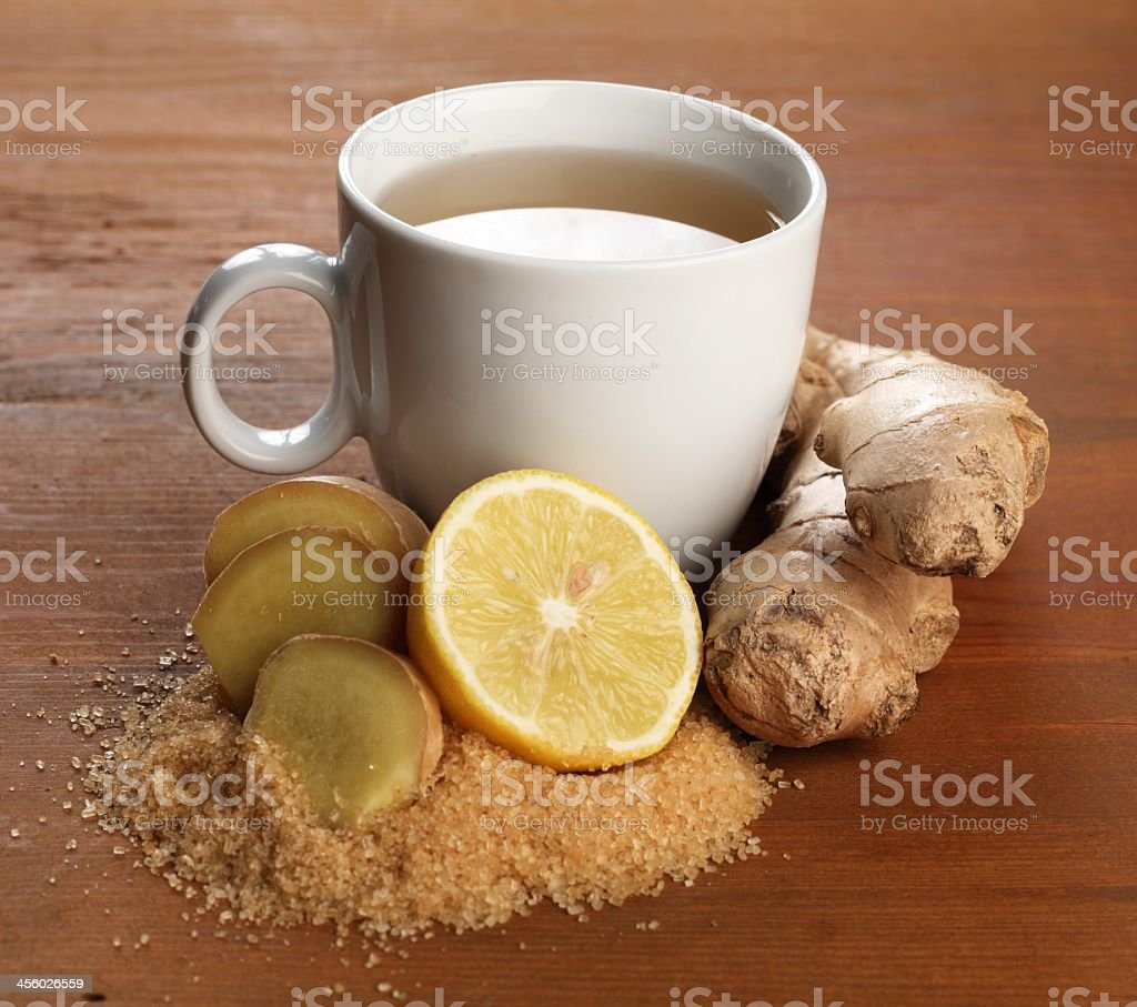 A white cup of ginger tea on a wooden table stock photo