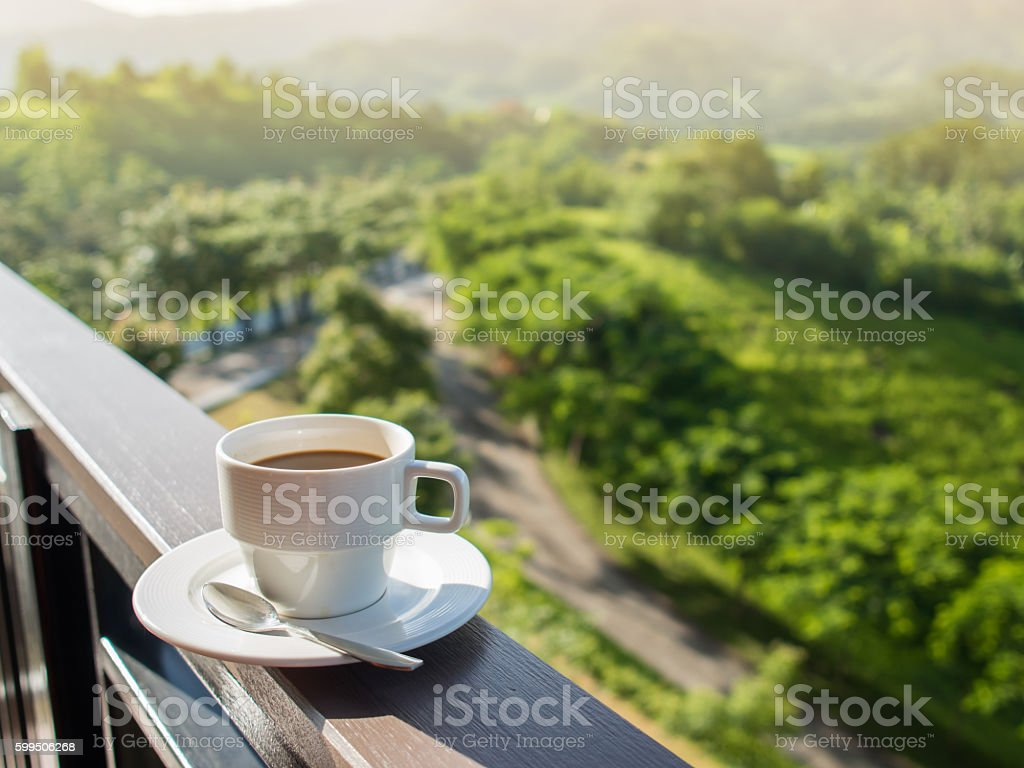 White cup of hot coffee on balcony with mountains. stock photo