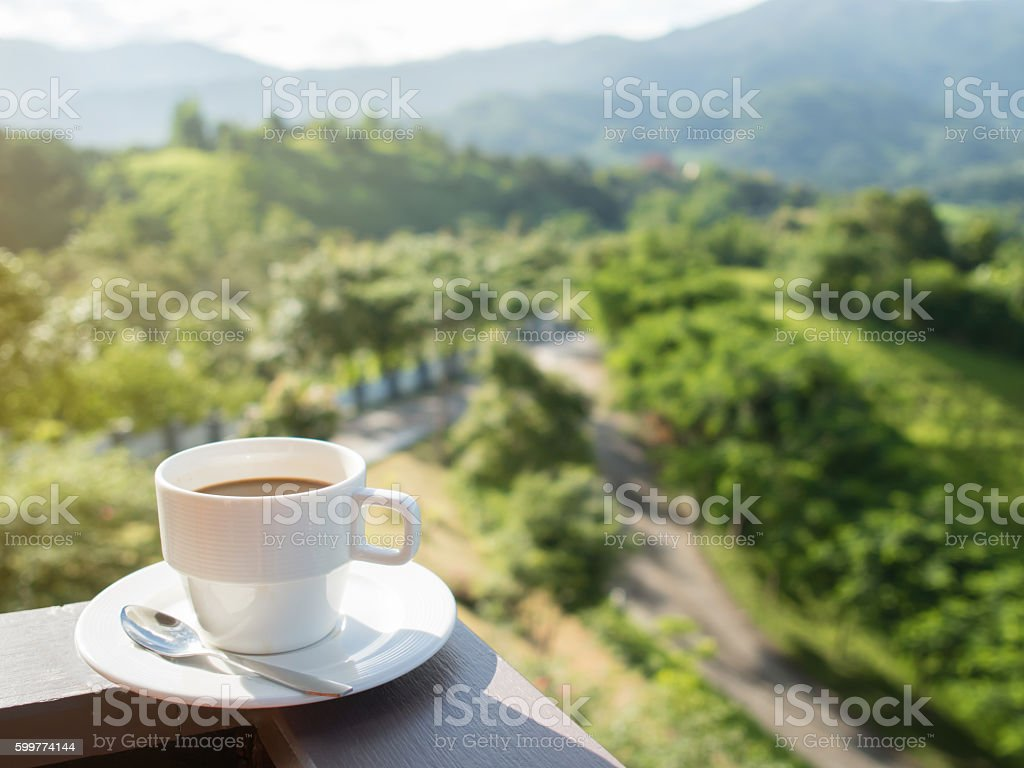 White cup of hot coffee with natural and mountains. stock photo