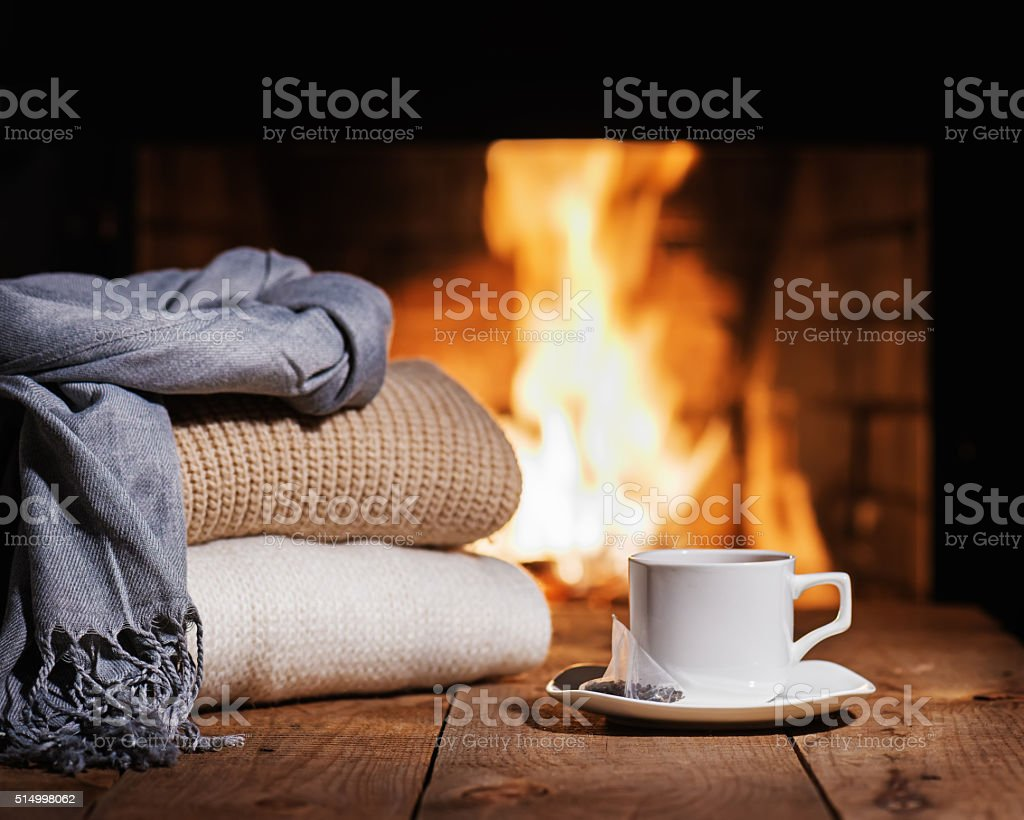 White cup of tea and warm woolen things near fireplace. stock photo