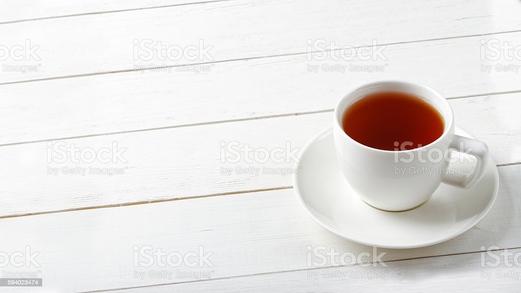 White cup of tea on a white wooden table. stock photo