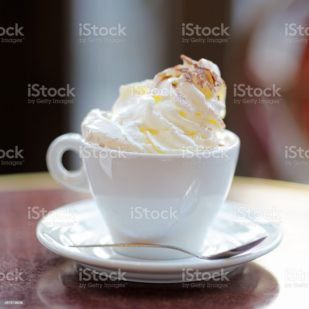 A white cup on a saucer with hot chocolate and whipped cream stock photo