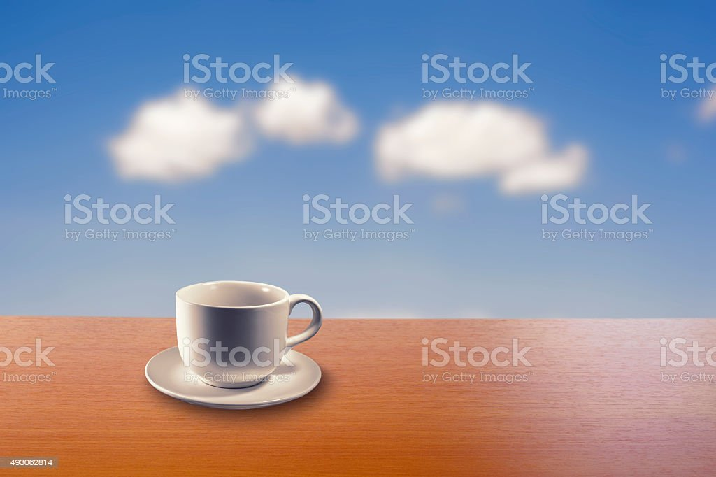 white cup on wood table with blue sky blurred background royalty-free stock photo