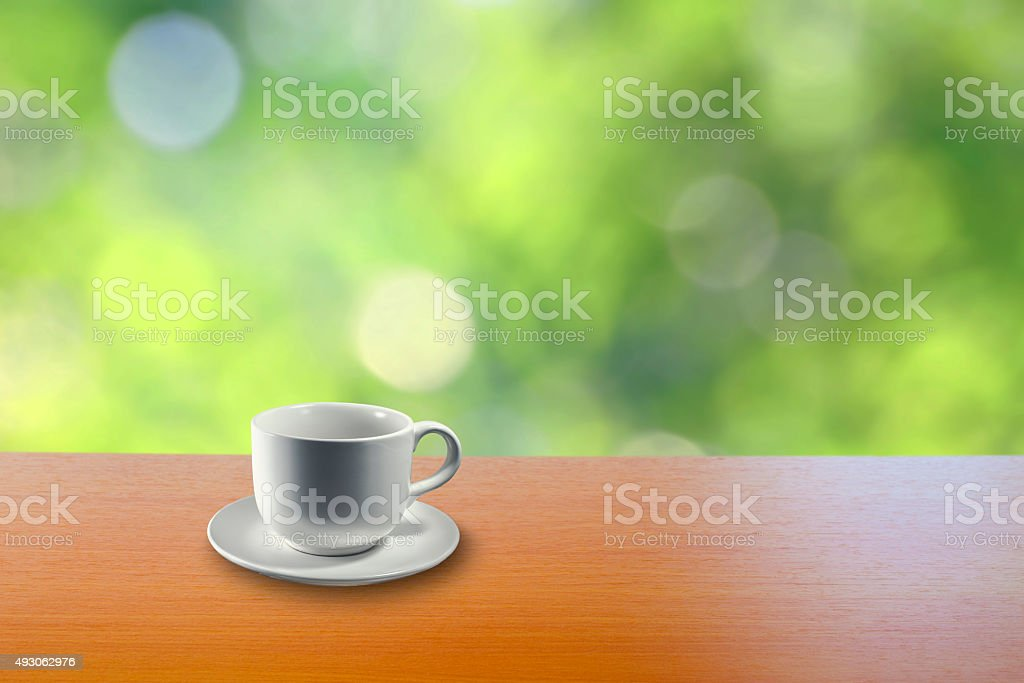 white cup on wood table with green blurred background royalty-free stock photo