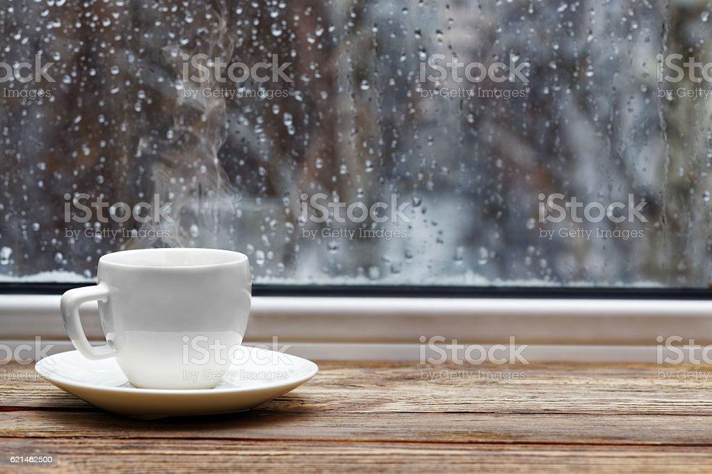 White cup on wooden windowsill stock photo