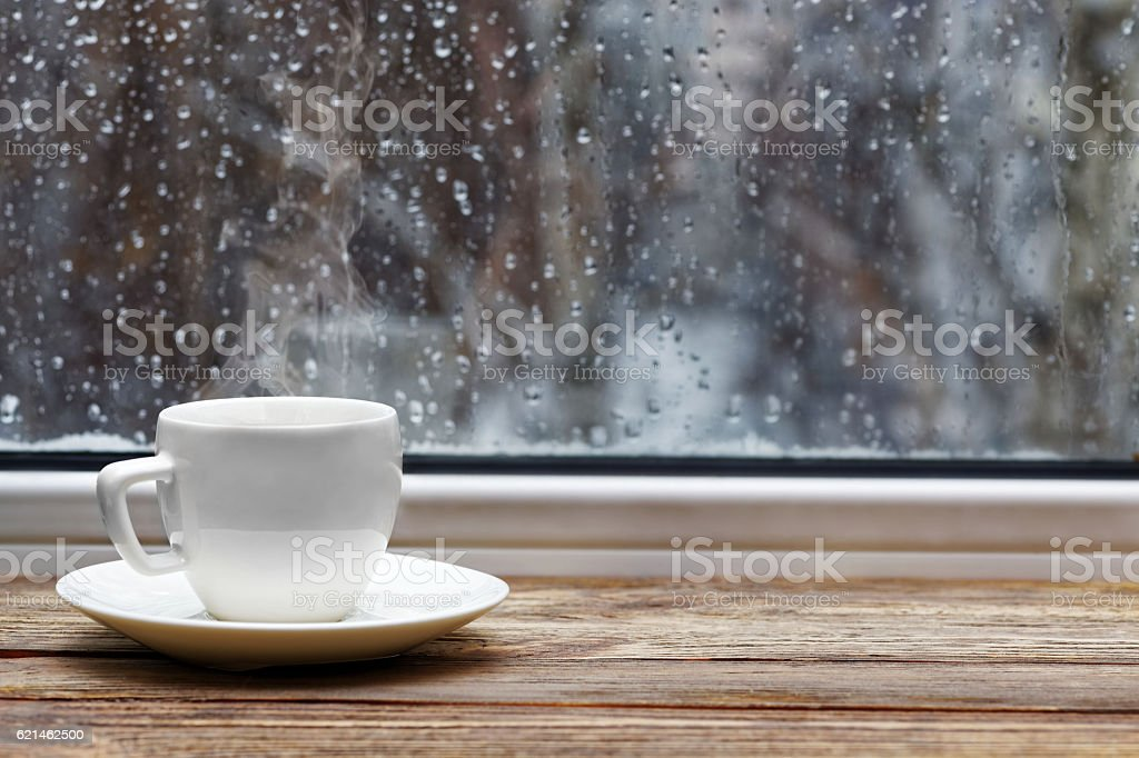 White cup on wooden windowsill stock photo