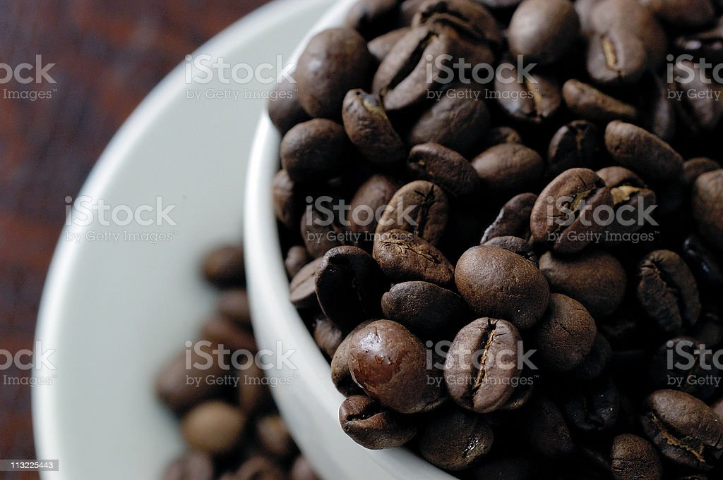 White cup overflowing with Columbian coffee beans royalty-free stock photo