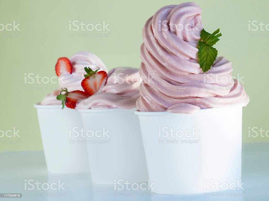 White cup overflowing with swirled strawberry soft serve stock photo