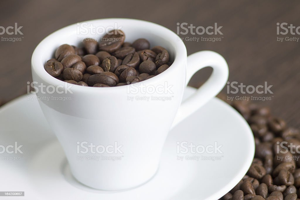 White cup with coffee beans royalty-free stock photo