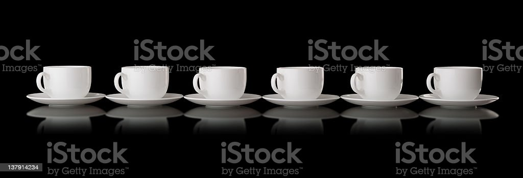 White cups and saucers on a black background royalty-free stock photo