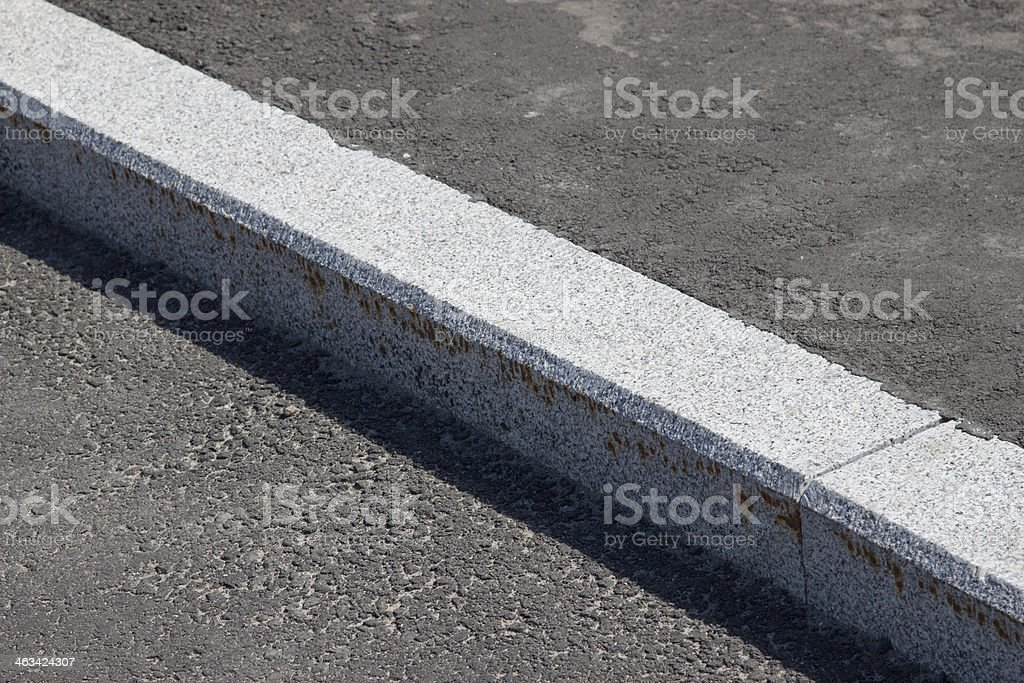 white curb and asphalt road stock photo