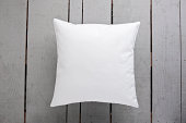 White cushion on wooden background