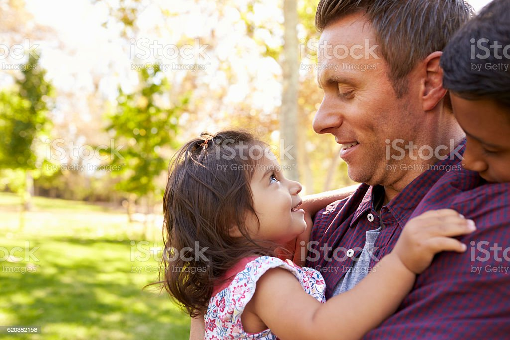 White dad with his two young mixed race children in stock photo