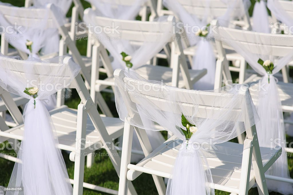 White decorated chairs on a green lawn stock photo
