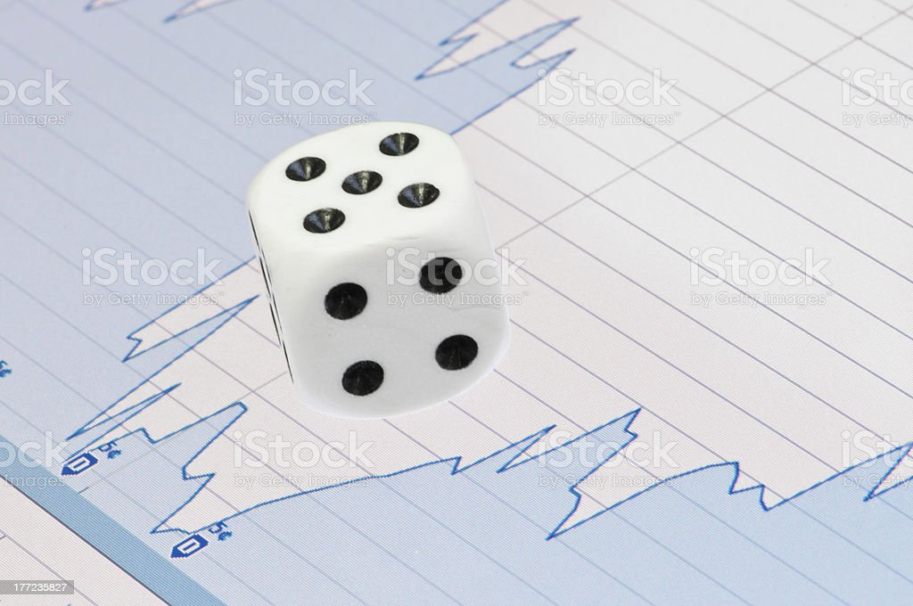 White dice on digital screen with financial chart stock photo