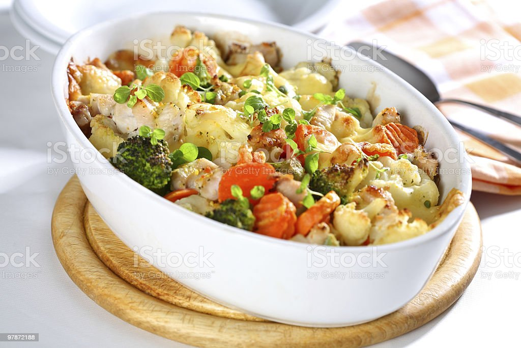 A white dish of baked mixed vegetables on a cutting board stock photo