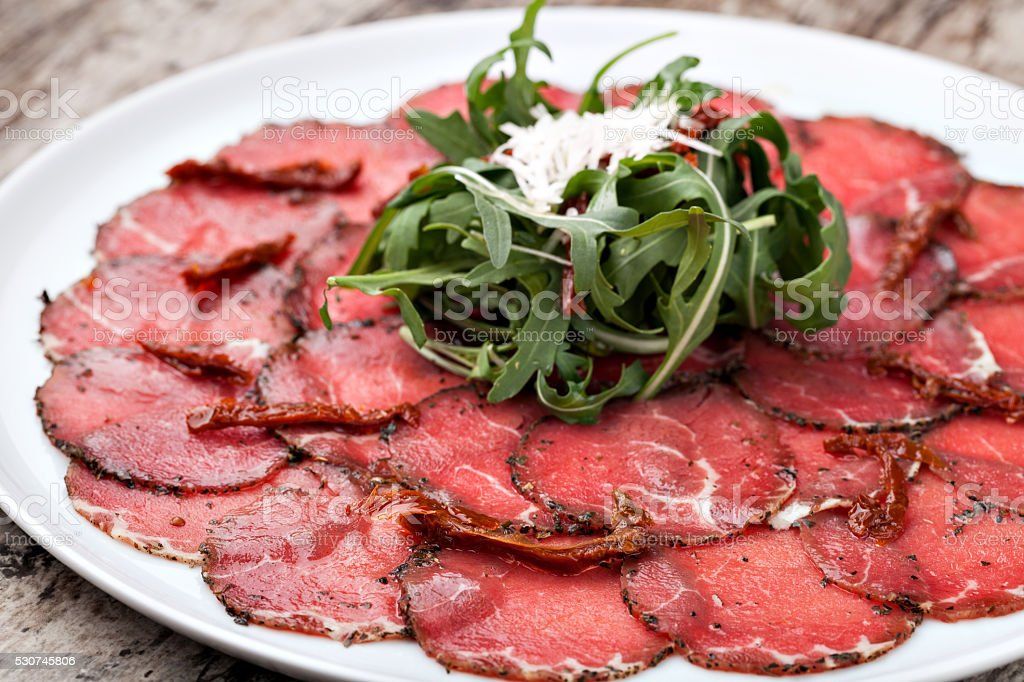 white dish with carpaccio of beef stock photo