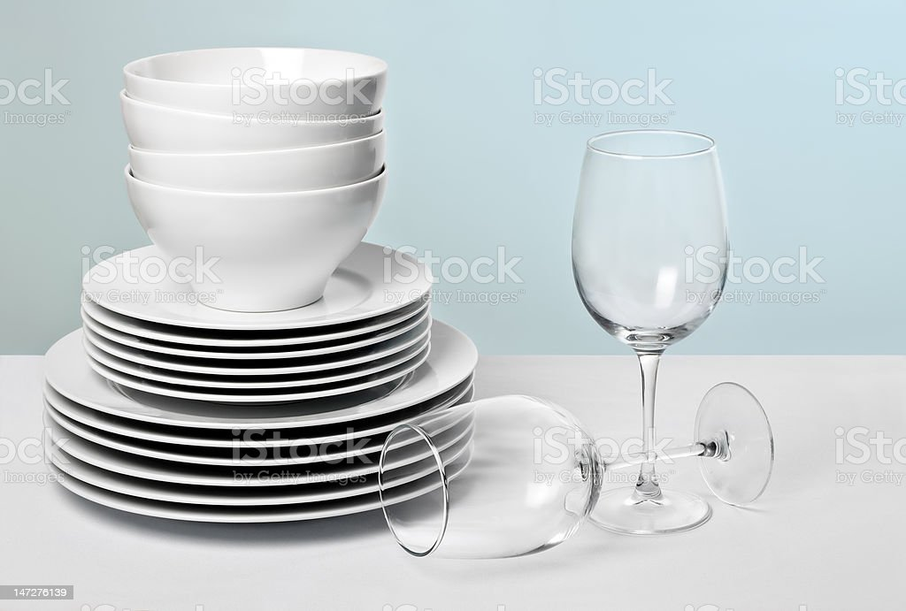 White dishes and crystal wine glasses on varied blue background stock photo