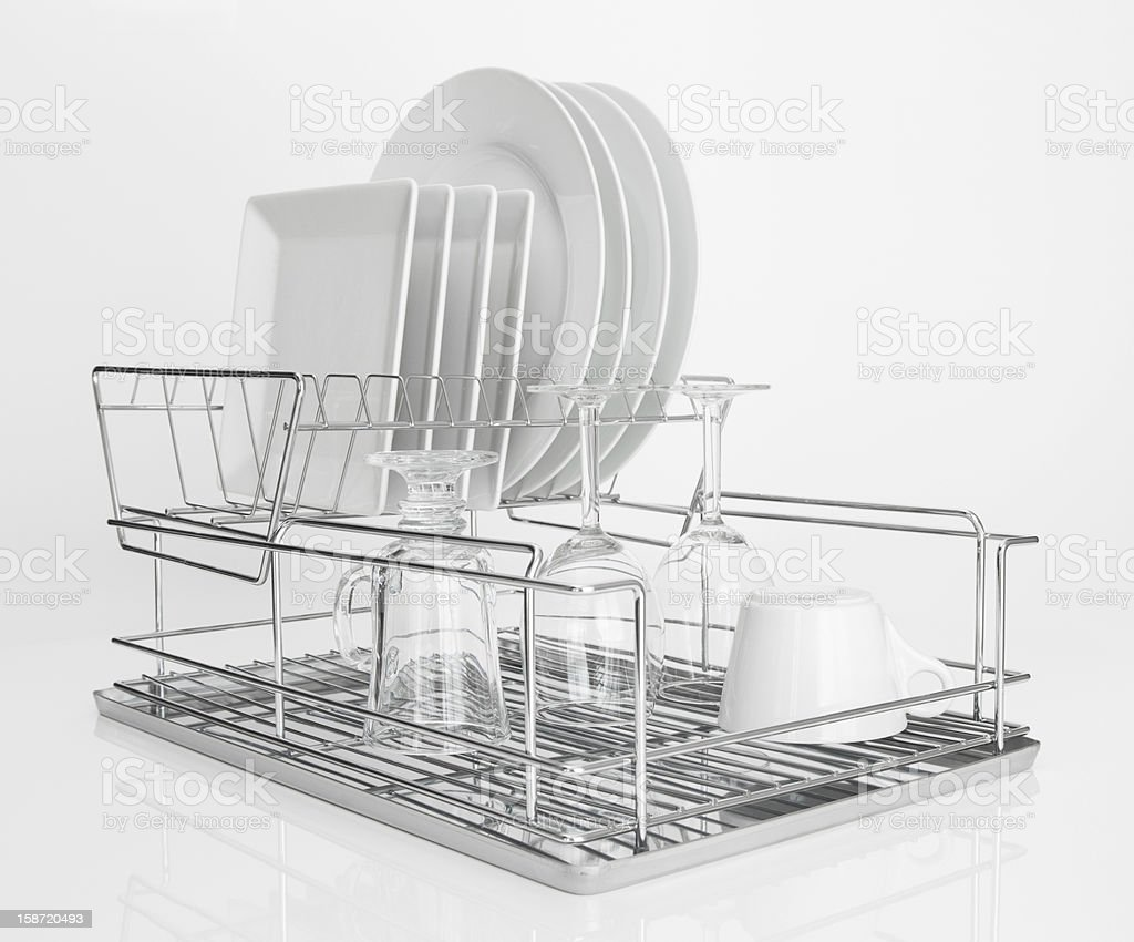 White dishes drying on metal dish rack stock photo