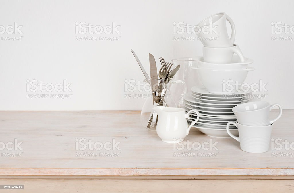 White dishware and cutlery on wooden table with copy space stock photo