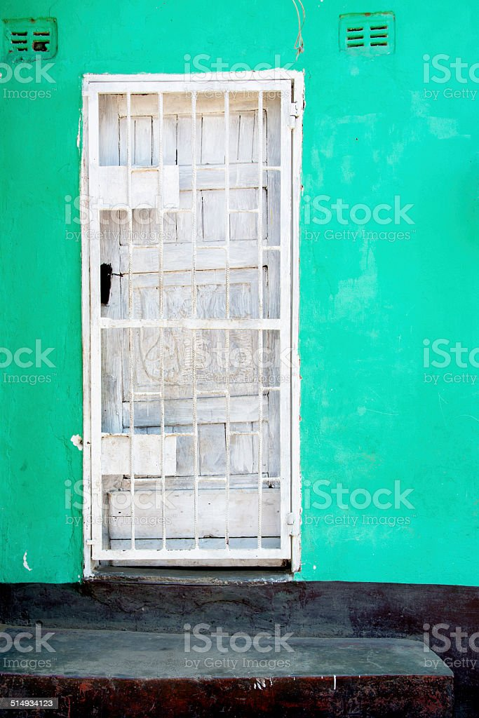 White door, Turquoise Wall, Black Steps stock photo