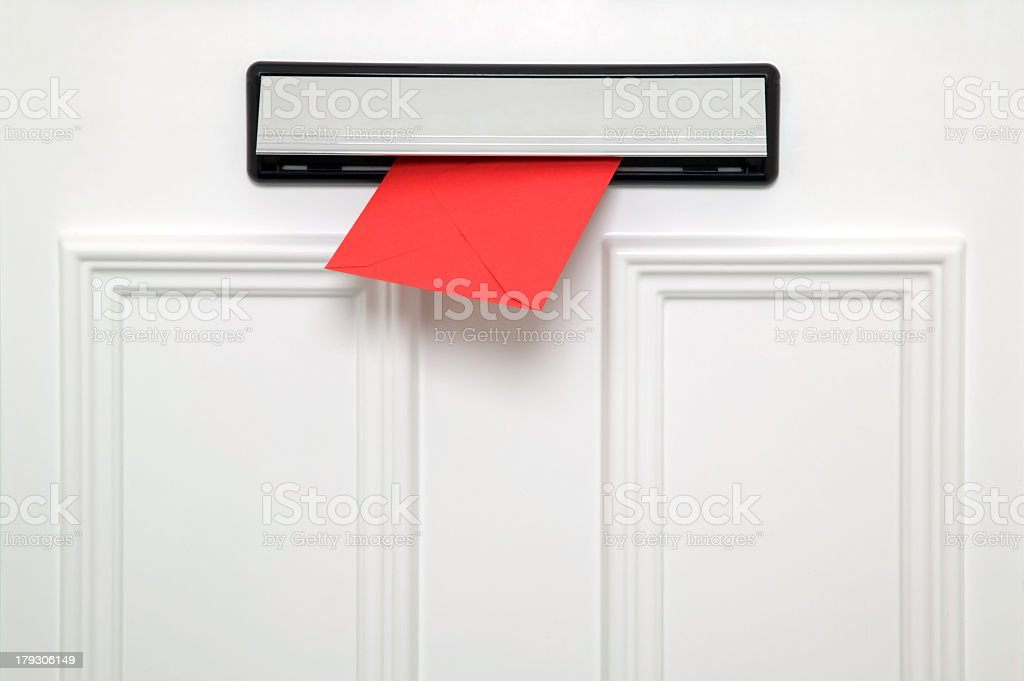 White door with a red envelope coming through the letterbox stock photo