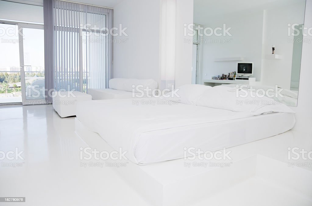 White double bed in white hotel room stock photo