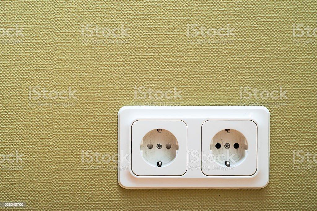 White dual socket on green wall stock photo