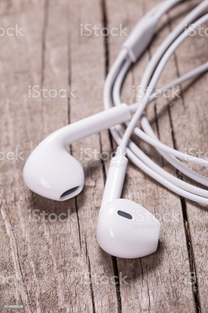 White earbuds on wooden table stock photo