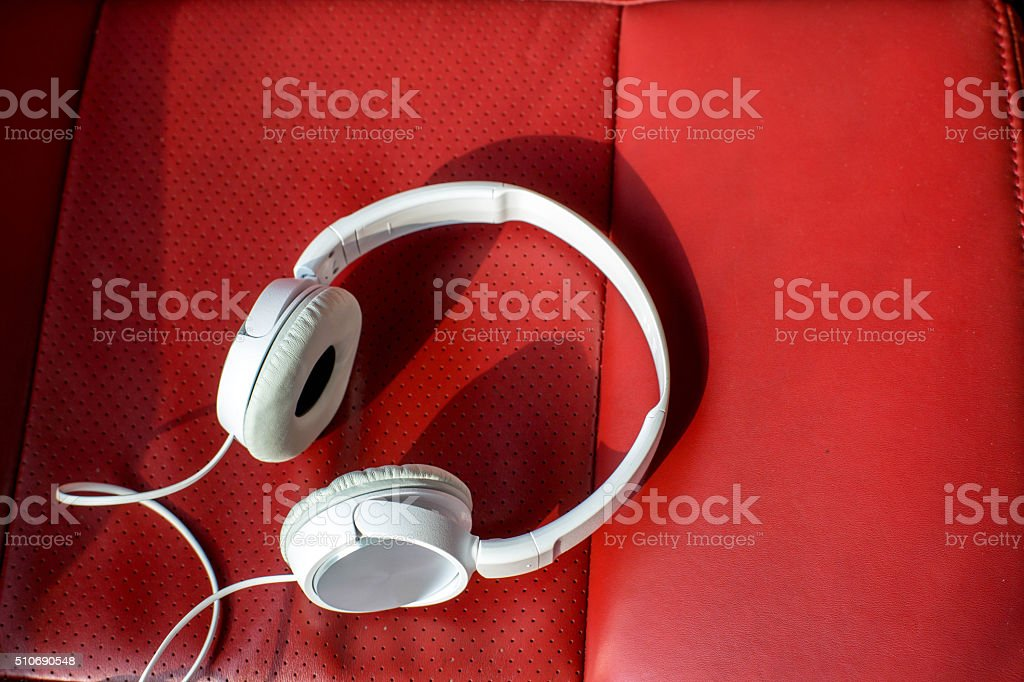 white earphone on red leather sofa stock photo