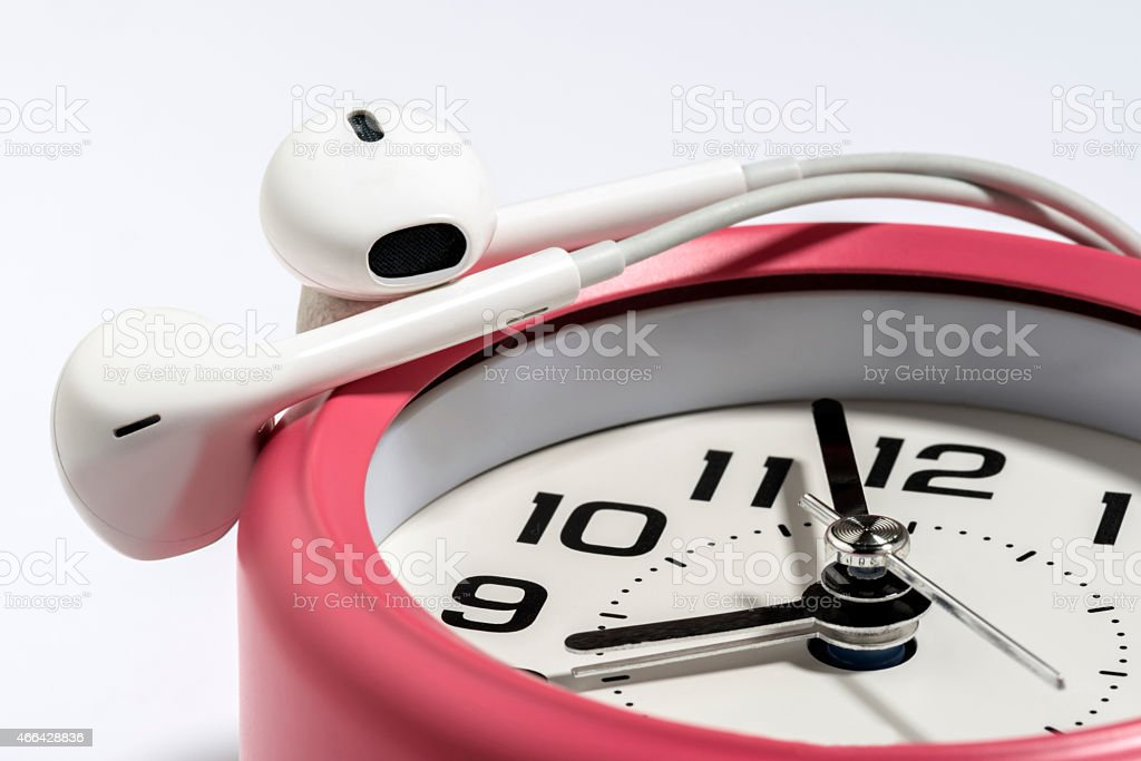 White Earphone with Pink Table Alarm Clock on White Background stock photo