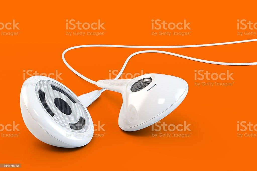 White earphones against orange background stock photo