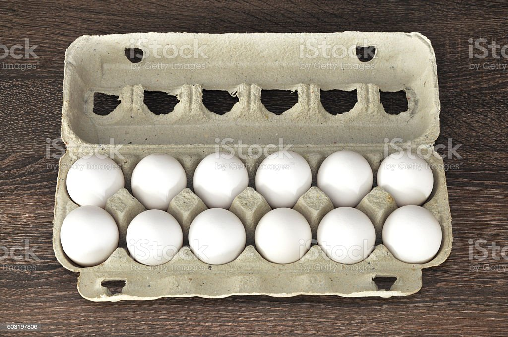 White eggs in box with a wooden background stock photo