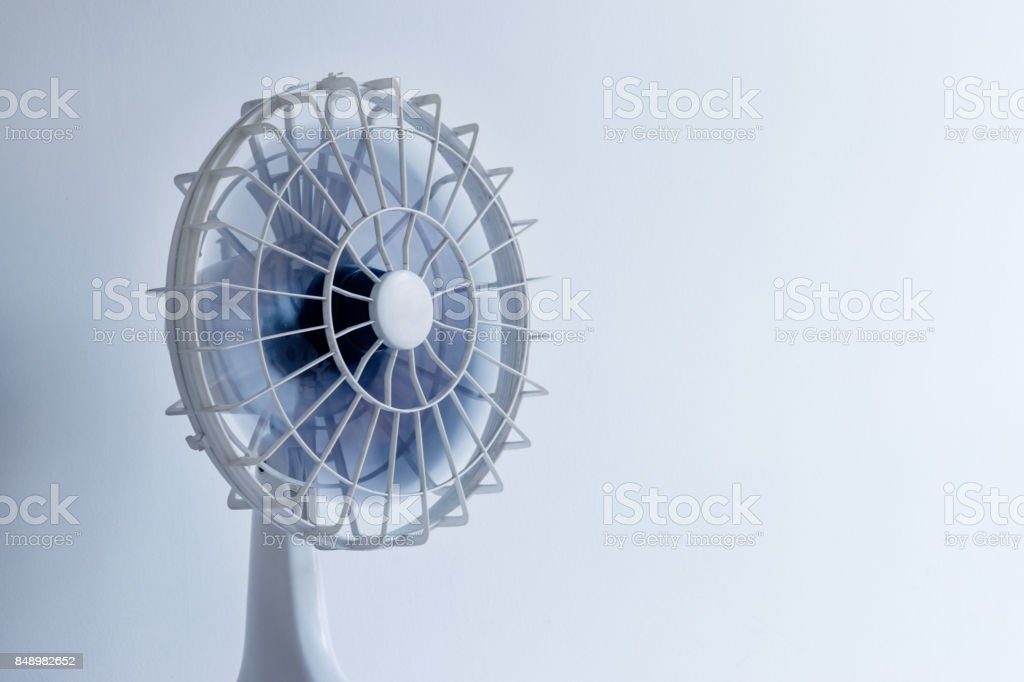 White electric fan, blue cyanotype tones, fan movement and blue, white and blue background stock photo