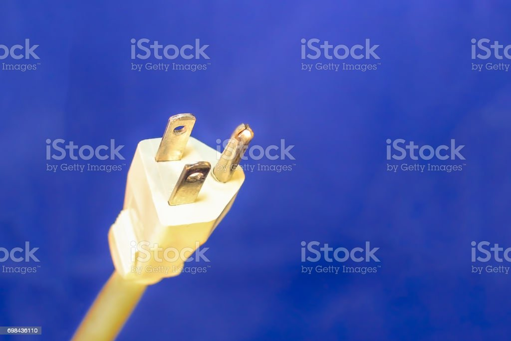 White Electrical Plug and Cord on Blue Background stock photo