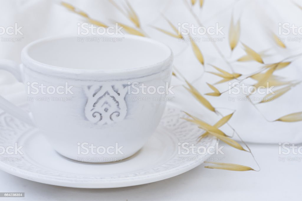 White elegant tea cup with saucer, dry plants, wild oats, white cotton fabric, styled image for social image, blogging stock photo