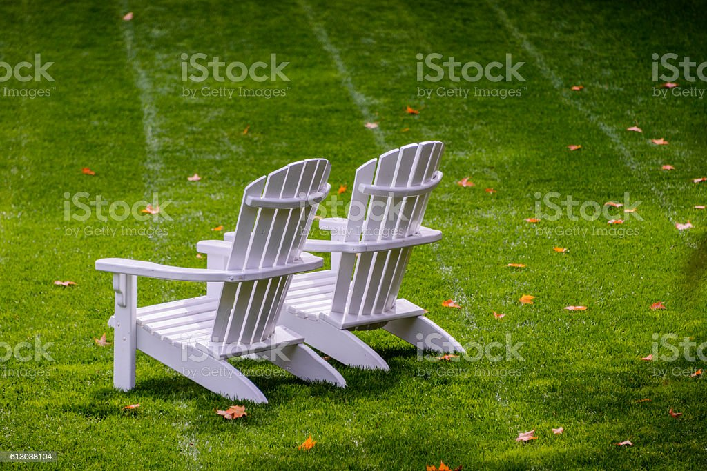 White empty Adirondack chairs on a green lawn stock photo