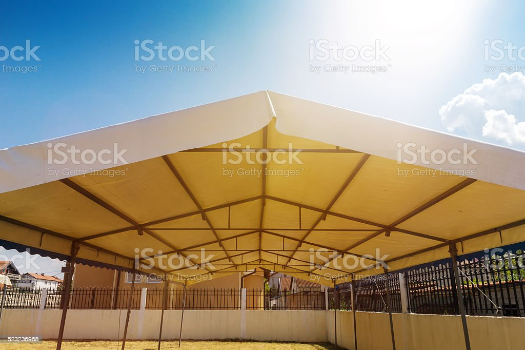 white entertainment tent in the garden in the sunlight stock photo